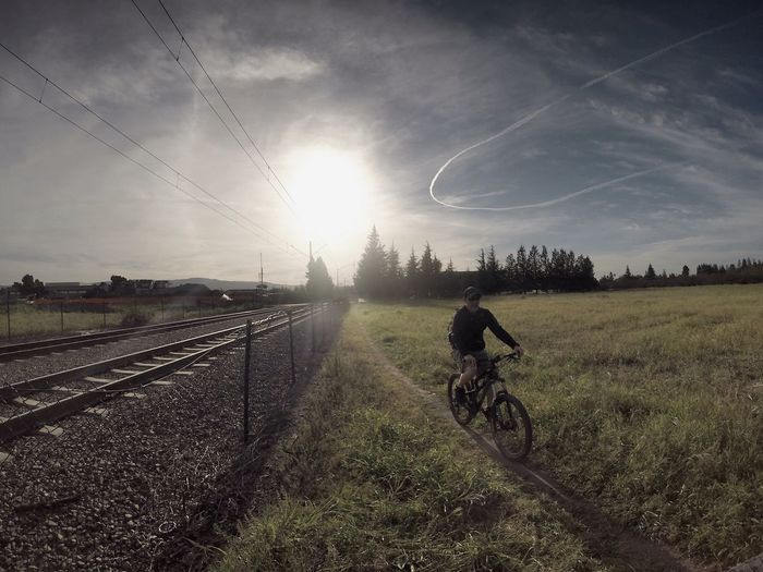 Man Cycling On Field By Railroad Tracks Against Sky During Sunny Day