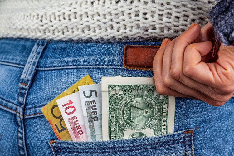 Midsection of woman putting paper currencies in pocket