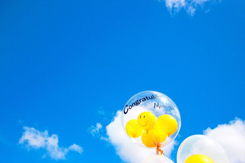 Low Angle View Of Balloons With Smiley Faces Against Sky