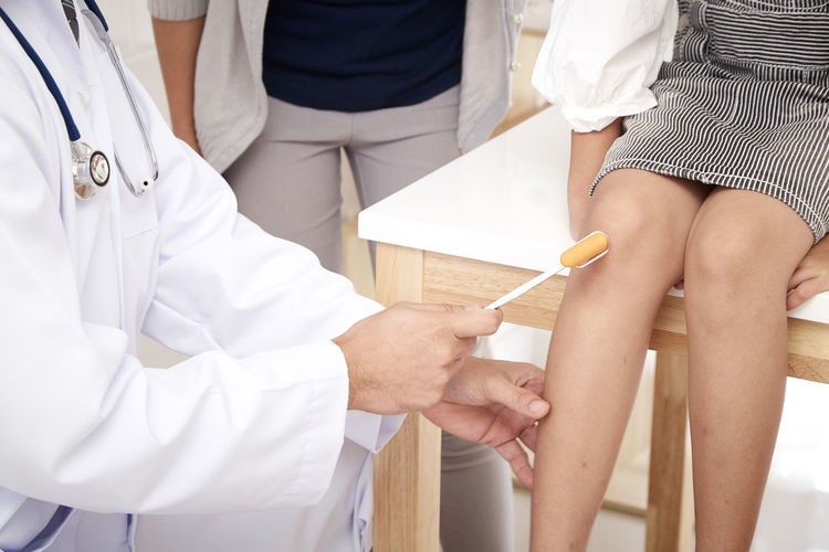 Cropped Image Of Doctor Examining Knee Of Patient In Clinic
