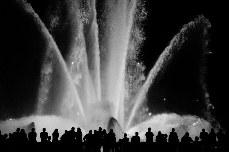 Silhouette crowd standing against illuminated fountain at night
