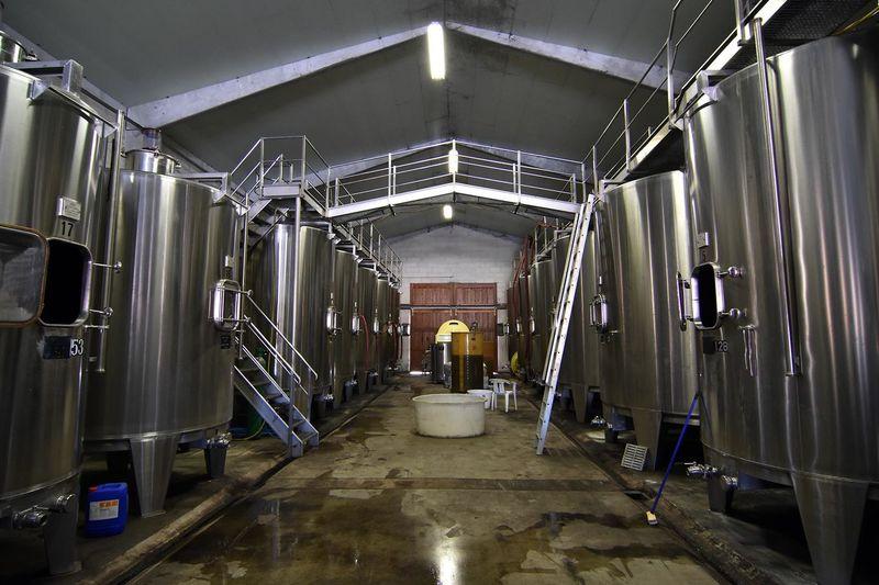 Aisle Amidst Metallic Storage Tanks At Winery