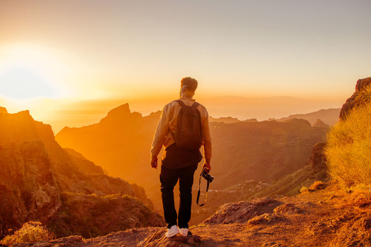 Rear view of man holding camera while standing on mountain against sky during sunset