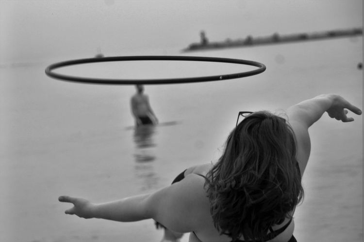 Woman with plastic hoop dancing at beach