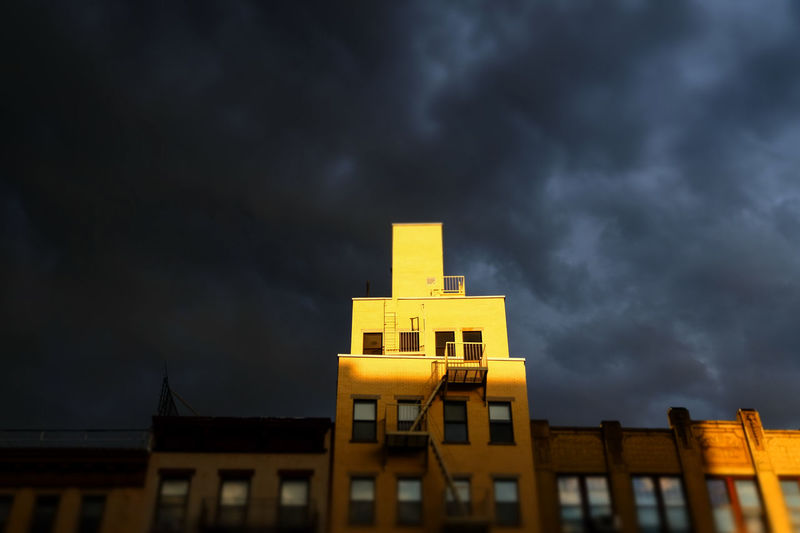 Low angle view of yellow building against cloudy sky