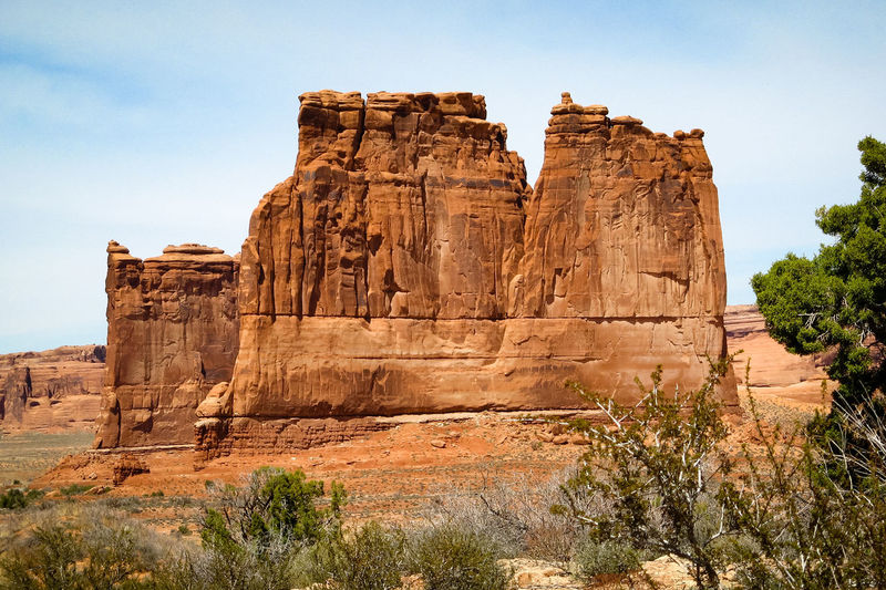 Plants and rock formations against sky at arches national park