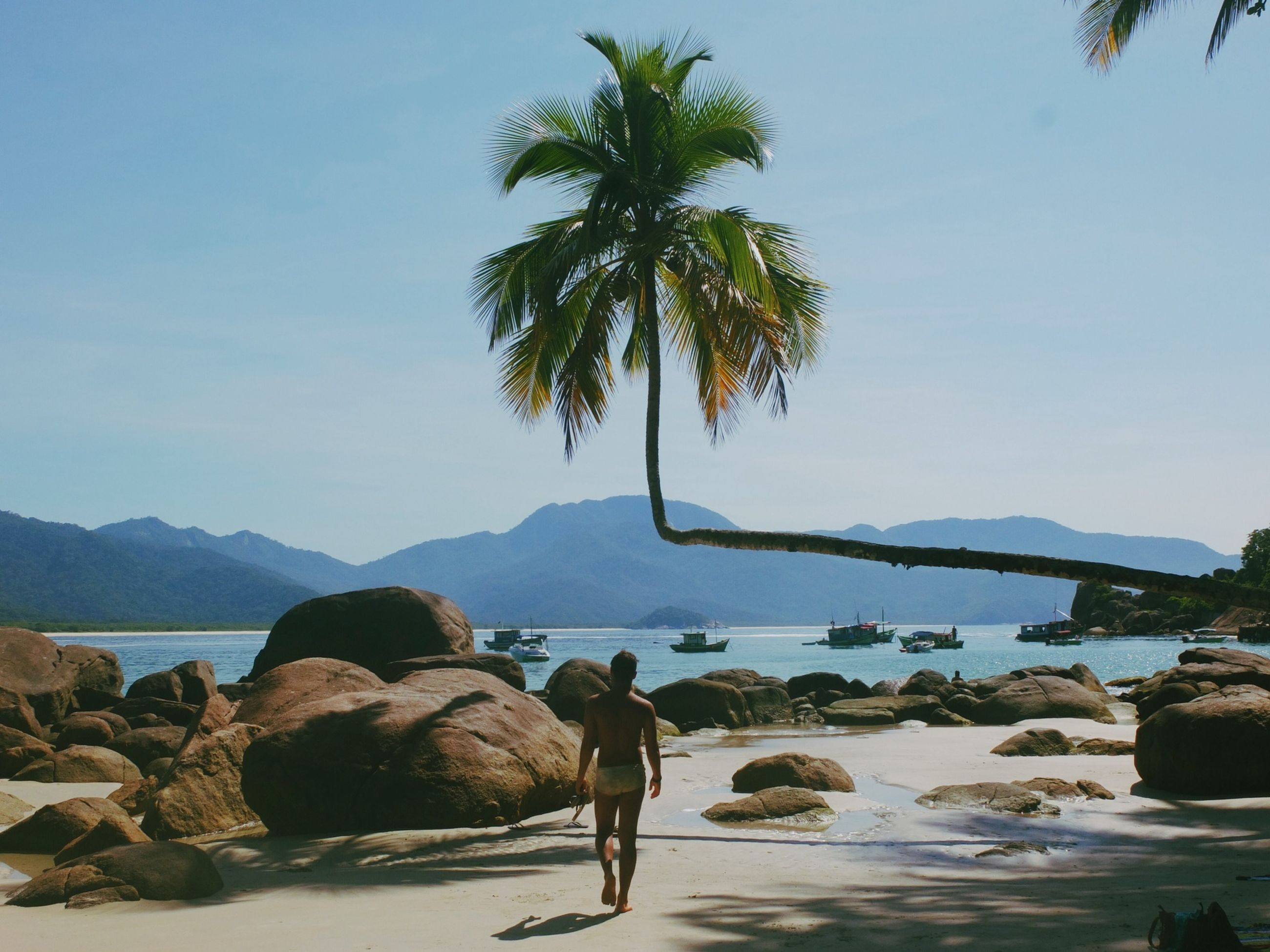 clear sky, water, mountain, tranquil scene, tranquility, copy space, tree, scenics, beauty in nature, nature, beach, rock - object, palm tree, sand, sea, idyllic, shore, men