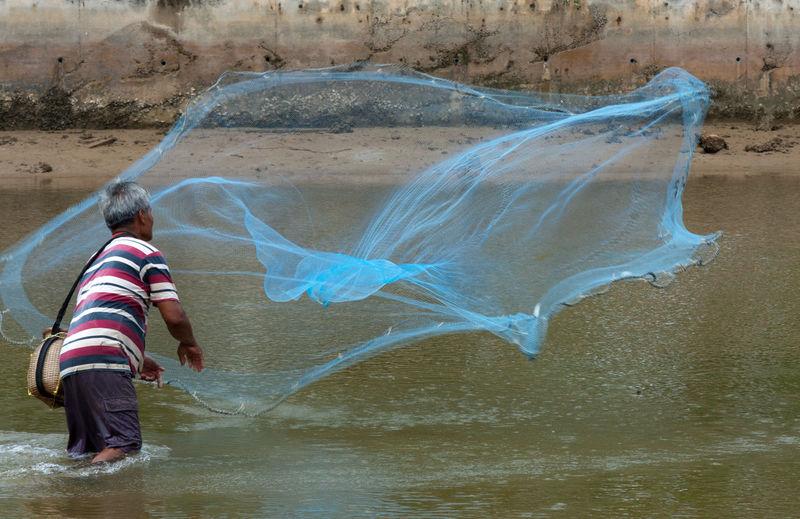 Man throwing fishing net in Phuket, Thailand Fisherman, Thailand, Phuket, Net, Thrown, Throwin