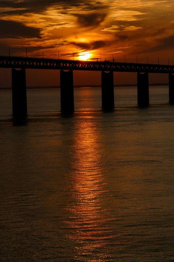 Bridge over sea against sky during sunset