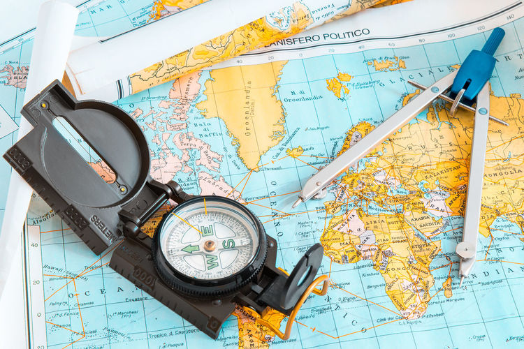 High angle view of navigational compass and drawing compass on world map