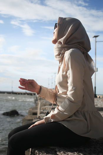 Moeslem Moeslemah Adult Clothing Cloud - Sky Day Hijab Hijabfashion Hijabstyle  Islam Leisure Activity Lifestyles Moeslimwomen Nature One Person Outdoors Real People Sea Side View Sitting Sky Water Women Young Adult Young Women The Portraitist - 2018 EyeEm Awards