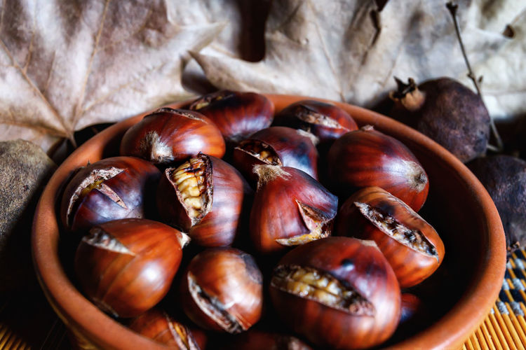 Roasted and cooked chestnuts ready to eat. in the background dry autumn leaves.