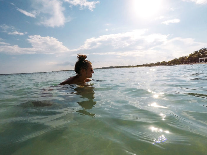 Young woman swimming in sea against cloudy sky