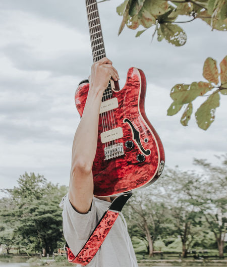 Midsection of man playing guitar against trees