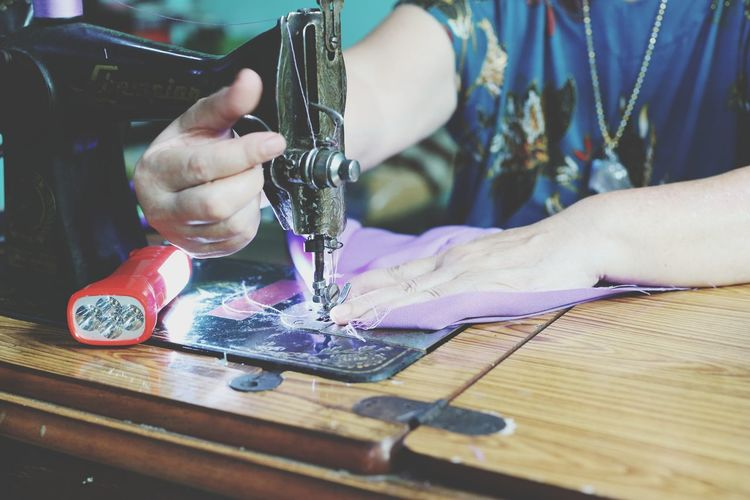 Midsection of woman using sewing machine at home