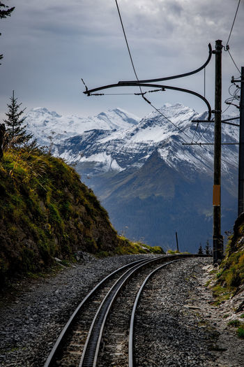 Railroad tracks by snowcapped mountains against sky