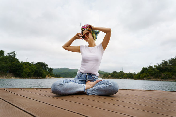 Full length of young woman sitting by lake against sky