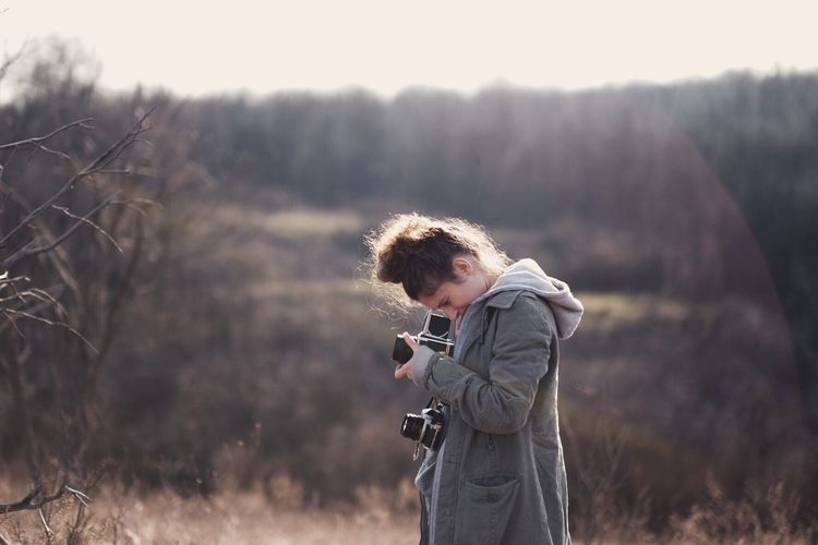 Side view of woman photographing through camera