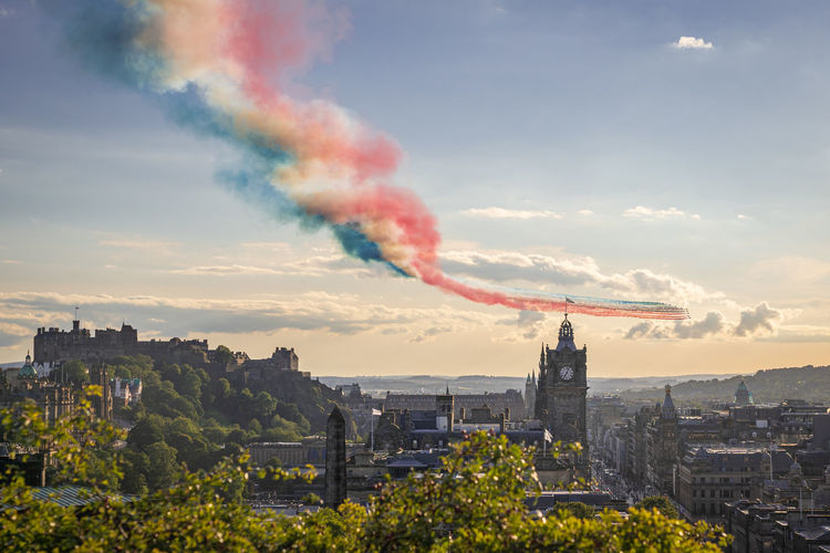 Red arrows flypast over edinburgh city in scotland at sunset.