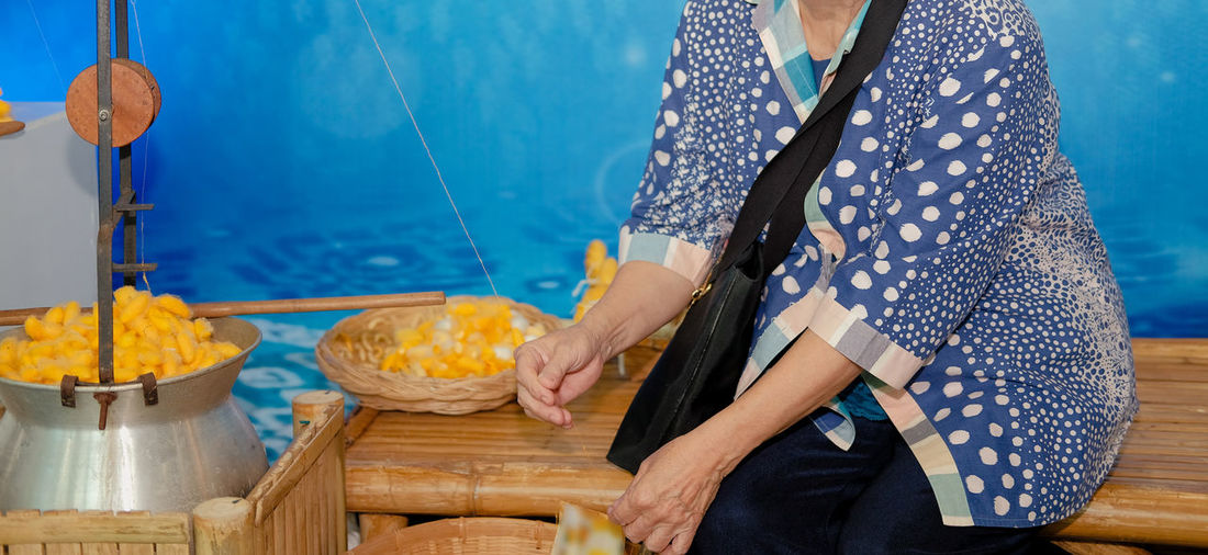 Midsection of woman making silk cloth from cocoons