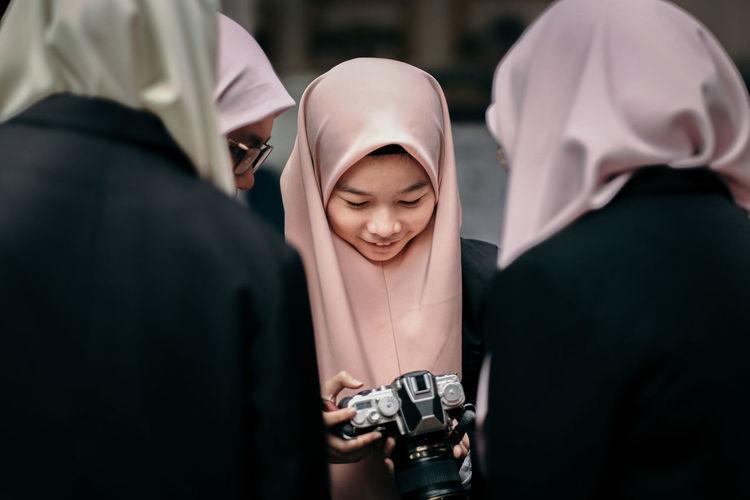 Teenage girl with women wearing hijab holding camera