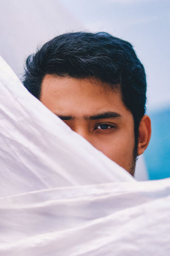 Close-up portrait of handsome young man face covered with sheet
