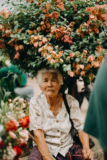 Plant Flower Women Flowering Plant Real People Senior Women One Person Lifestyles Senior Adult Front View Leisure Activity Adult Day Waist Up Nature Looking At Camera Three Quarter Length Plant Part Outdoors Hairstyle