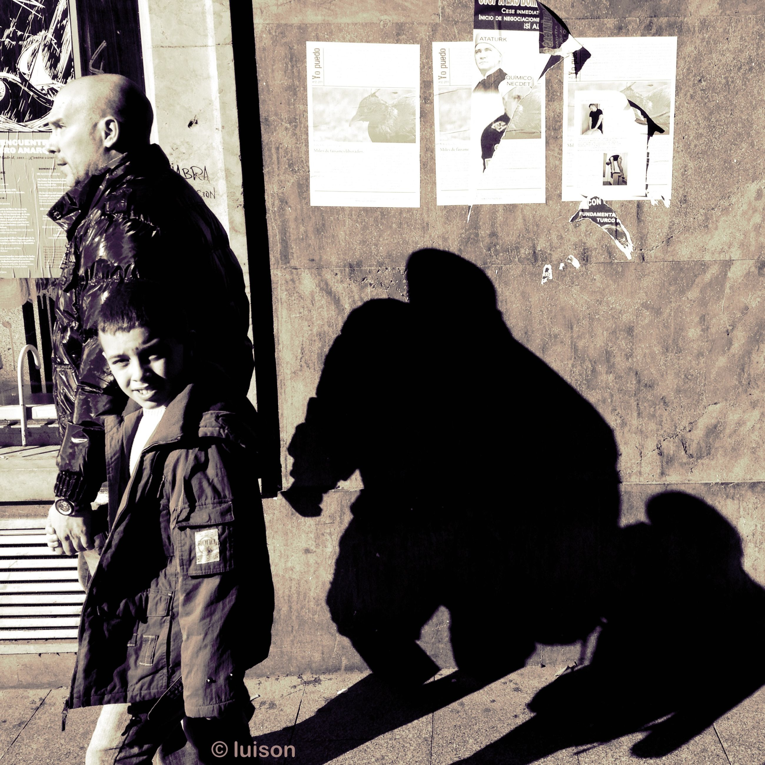 lifestyles, building exterior, built structure, architecture, leisure activity, wall - building feature, togetherness, text, human representation, street, communication, standing, full length, bonding, love, outdoors, day, shadow