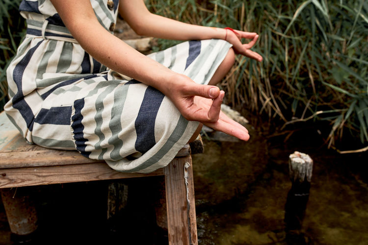 Young woman in dress meditating on the nature person