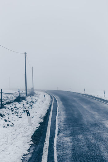 Empty road leading towards snow covered landscape against sky