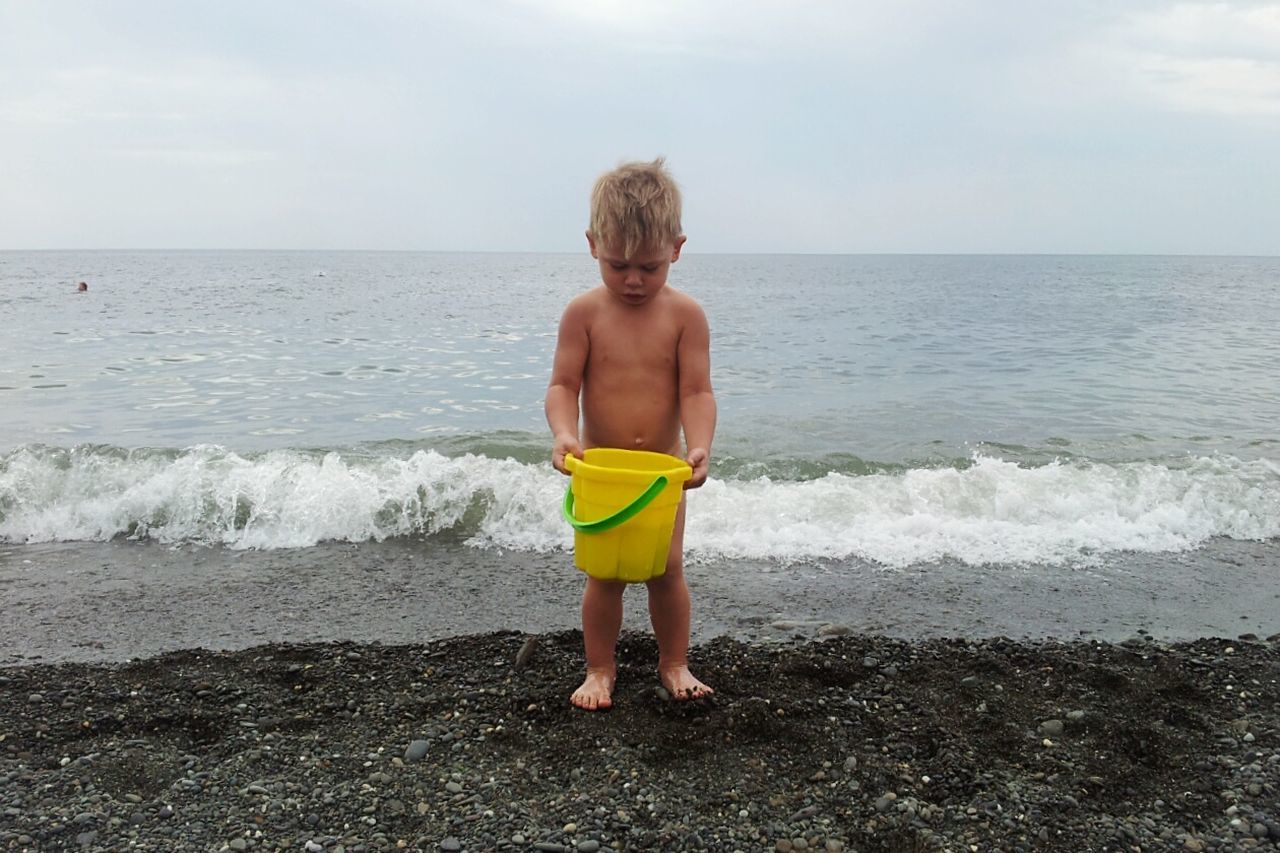 sea, shirtless, boys, beach, one person, real people, childhood, horizon over water, water, leisure activity, standing, sky, vacations, elementary age, rear view, beauty in nature, nature, full length, lifestyles, day, one boy only, outdoors, scenics, wave, blond hair, sand pail and shovel, young adult, people