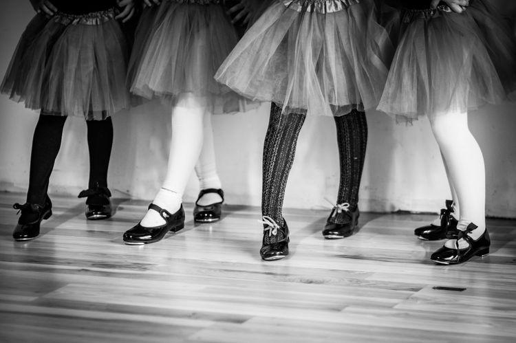 Little girls line up for dance practice with fancy leggings. Dancing Teaching Activity Ballarina Black And White Dance Floor Dance Photography Feet Girls Knees Leggings Little Girl Shoes Skirts Tap Shoes Wood Floors