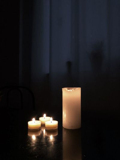 Close-up of lit candles on table in darkroom