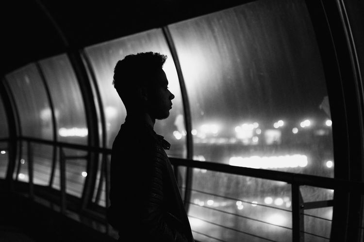 Silhouette man standing on bridge at night