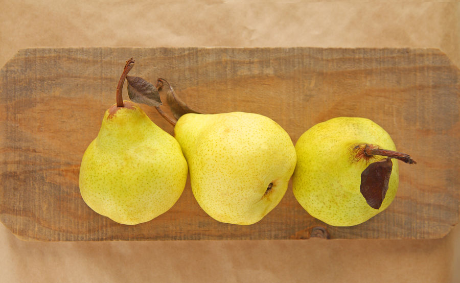 Three pears from overhead Copy Space Natural Light Textures Close-up Day Food Fresh Fruit Harvest Healthy Eating Indoors  No People Organic Overhead Pale Green Pear Ripe Room For Text Seasonal Studio Shot Wood Surface