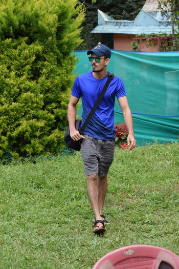 Full length of young man wearing sunglasses standing on grass