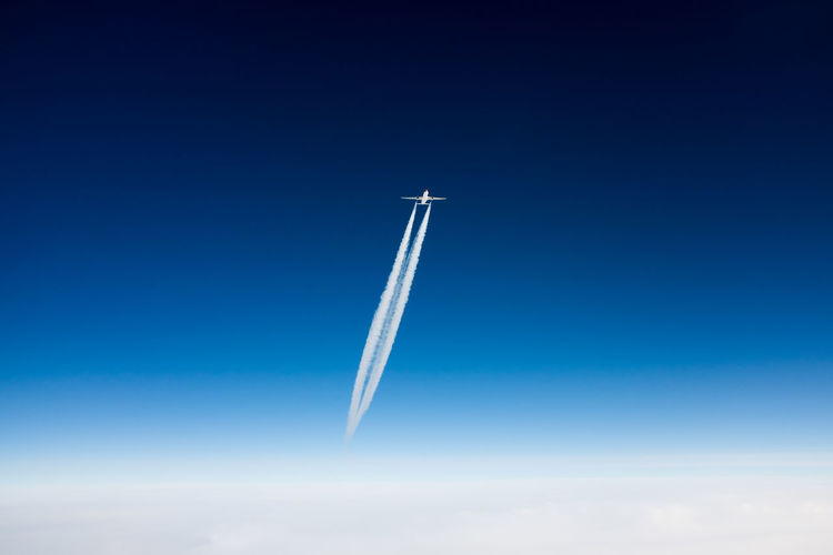 Airplane and vapor trail against sky