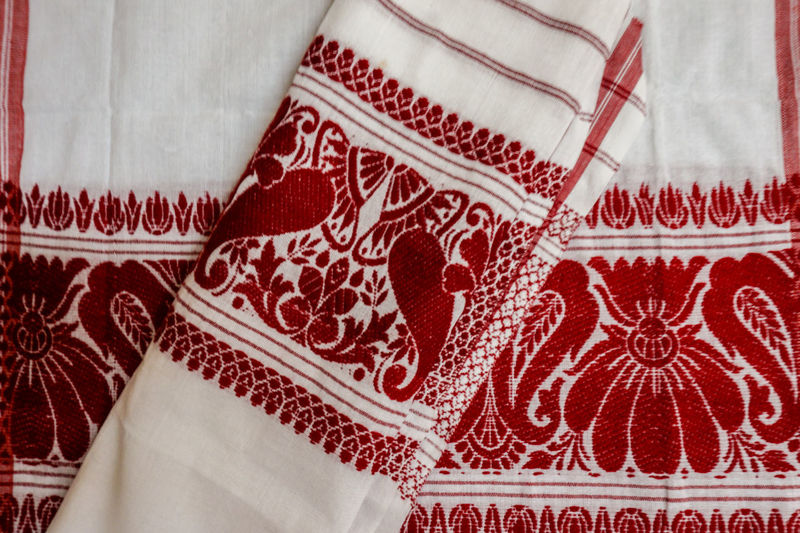 """THE FULAM GAMOSA"" :It is generally a white rectangular piece of cloth with primarily a red border on three sides and red woven motifs on the fourth (in addition to red, other colors are also used). Although cotton yarn is the most common material for making/weaving gamosas, there are special occasion ones made from Pat silk. Assamese Traditional Close-up Clothing Colors And Patterns Cotton Culture And Tradition Culture Of Assam Design Designs Full Frame Gamosa Hand Woven Handicraft I Indoors  Northeastindia Pattern Textile Traditional Clothing"