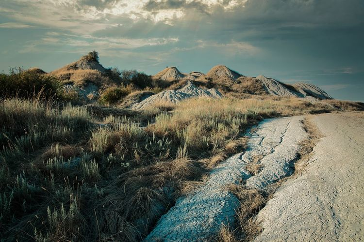 Scenic view of tuscany clay hills against dramatic sky