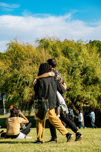 Rear view of people photographing against trees