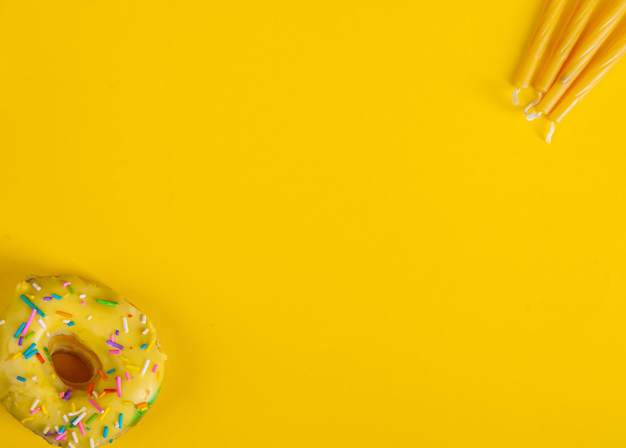 HIGH ANGLE VIEW OF MULTI COLORED CANDIES ON YELLOW BACKGROUND