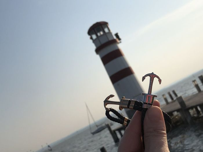 Cropped hand of person holding small anchor against lighthouse at beach