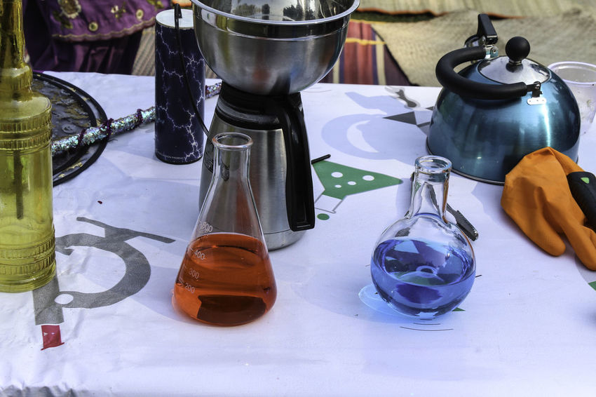 Beakers and jars and other equipment, of different sizes and shapes, for a scientific demo. These are typically demos meant for children, to start getting them interested in the science. A lot of these experiments and demos use liquid nitrogen and other liquids and gases; these experiments could be of instant freezing using liquid nitrogen, and so on. The table is at the start of the session, where the equipment needed is getting readied. Beaker Beakers Blue Liquid Equipment Glass Equipment Jar Jars  Red Liquid Science Demo Science Experiment Scientific Experiment Table Table Cloth