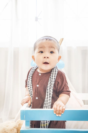 Cute baby boy looking away while standing in crib at home