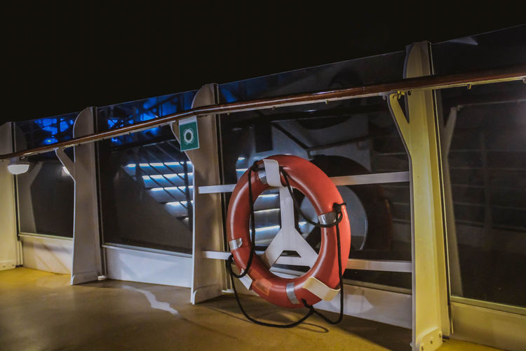 View of red lifebuoy on cruise ship balcony deck with railing at night. Tropical vacation getaway on sea. No People Night Technology Illuminated Modern Indoors  Architecture Transportation Arts Culture And Entertainment Communication Mode Of Transportation Travel Railing Reflection Connection Light - Natural Phenomenon Seat Safety Equipment Cruise Cruise Ship Boat Ship Travel Safety First! Lifebuoy