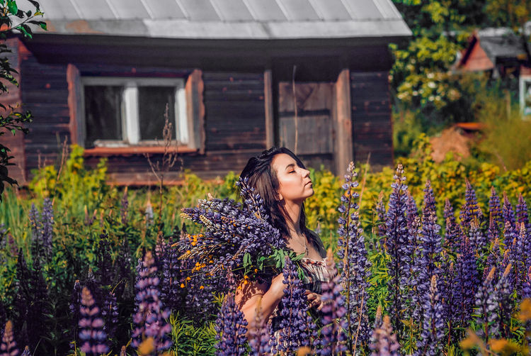 Woman standing in front of flowering plants in yard