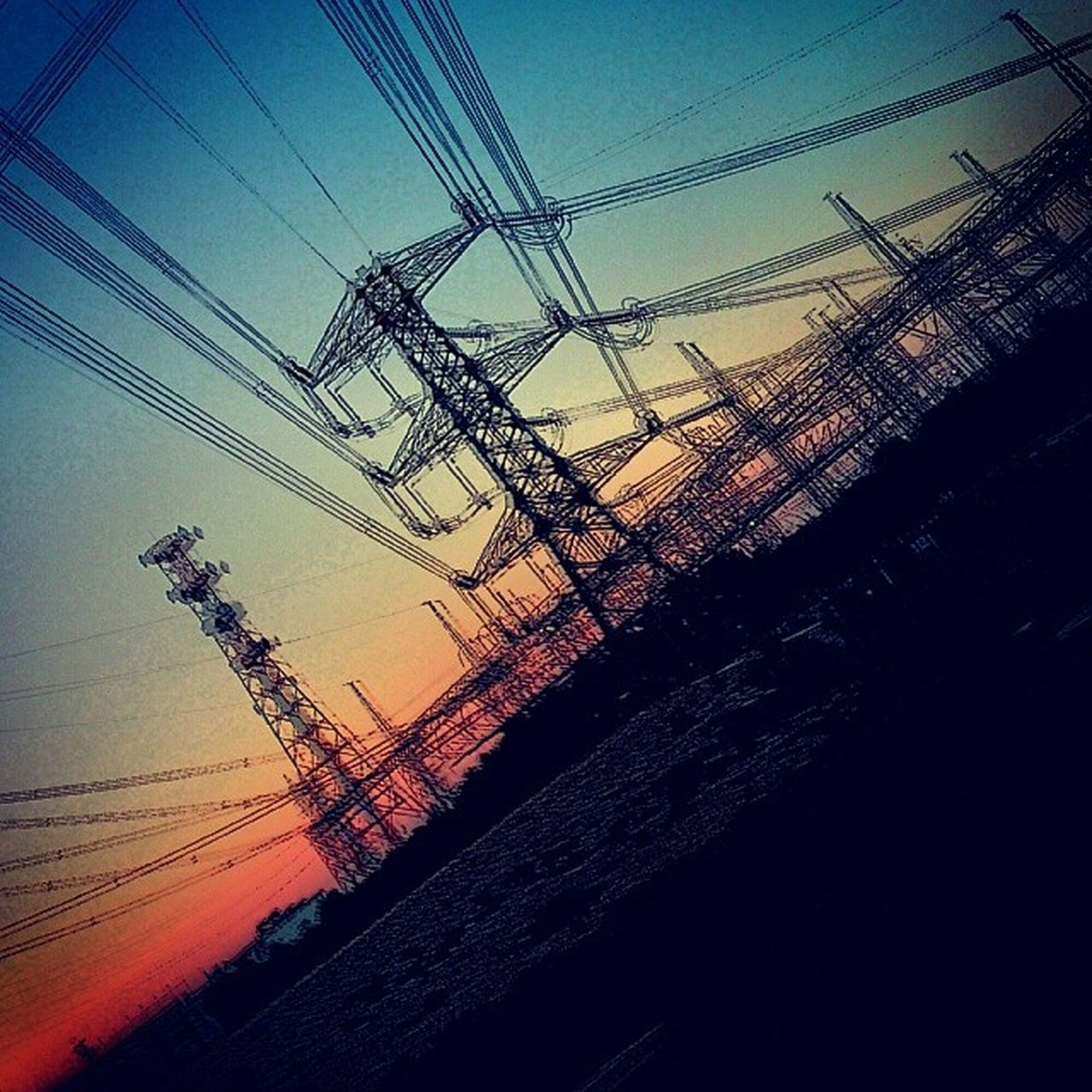 connection, power line, electricity pylon, electricity, cable, power supply, built structure, low angle view, architecture, sky, technology, silhouette, sunset, clear sky, fuel and power generation, dusk, building exterior, outdoors, blue, no people