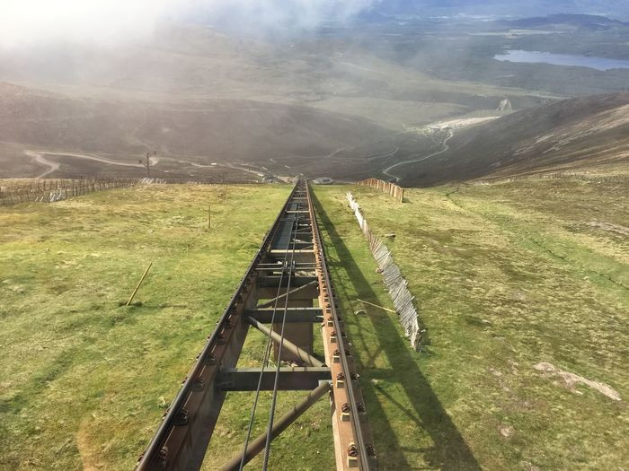 Railroad track at cairngorm mountains on sunny day
