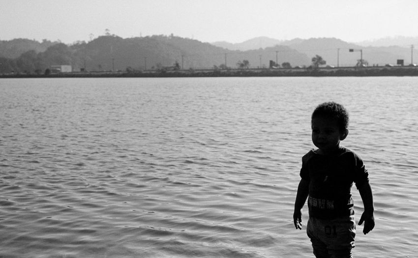 Silhouette Boy Standing By Sea Against Clear Sky