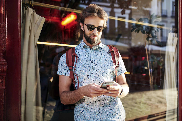 Man wearing sunglasses using mobile phone outdoors